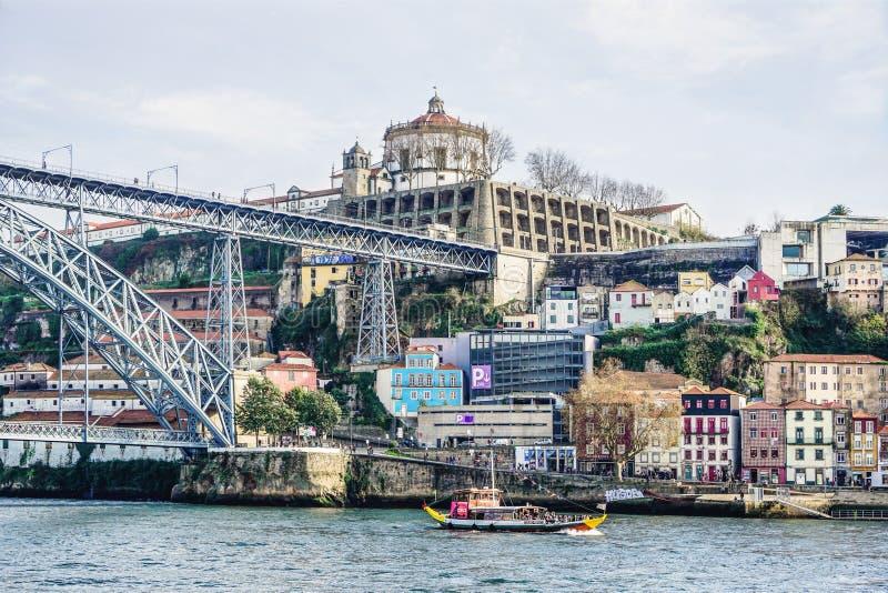 Porto Portugal - December 2018: Rabelo fartyg med turister i den Douro floden Luis I bro och kloster av Serra att göra Pilar royaltyfri foto