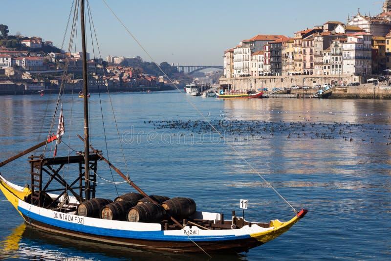 PORTO, PORTUGAL - JANEIRO 18,2018: Barcos que levam tambores do embarcadouro visto vinho de Porto no banco de rio Opinião do pano fotos de stock