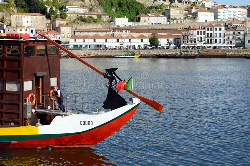 Embankment of the Douro River. Silhouette of a woman and the flag of Portugal on the bow of a wooden boat. Porto, Portugal, June 2019. Embankment of the Douro royalty free stock images