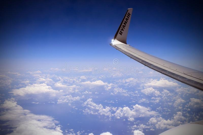 White fluffy clouds in the blue sky under the wing of the aircraft of the airline Ryanair. stock photos