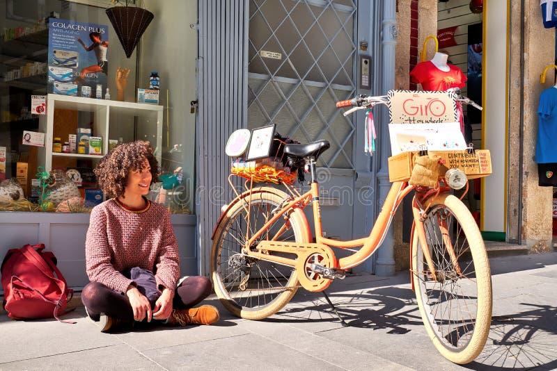 PORTO, PORTUGAL - MAART 26, 2018: Portret van glimlachende vrouw op straat met fiets, kunstenaars` s winkel stock afbeelding
