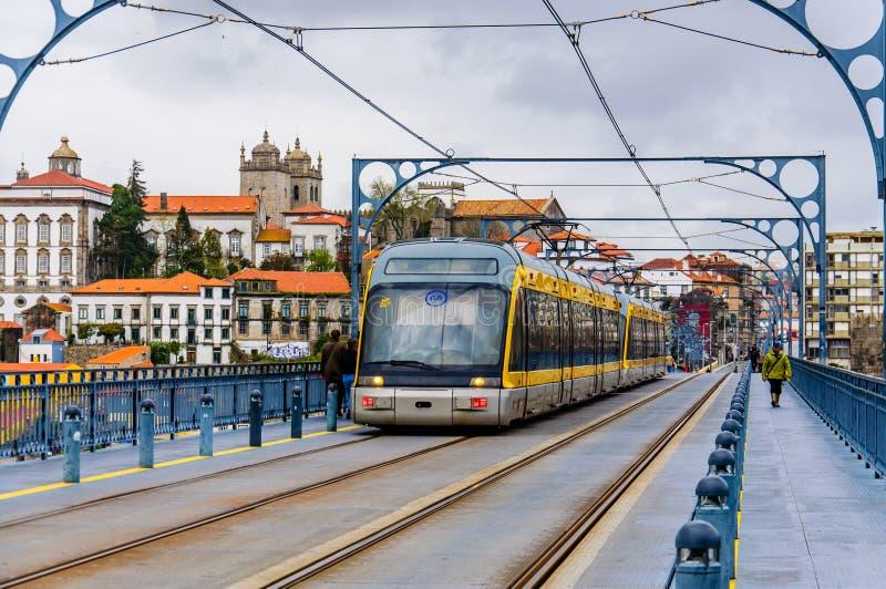 Porto metro tram on the bridge. Porto / Portugal - March 29 2016: Public transportation. Modern metro tram driving along Luis I Bridge on the tramline royalty free stock photography