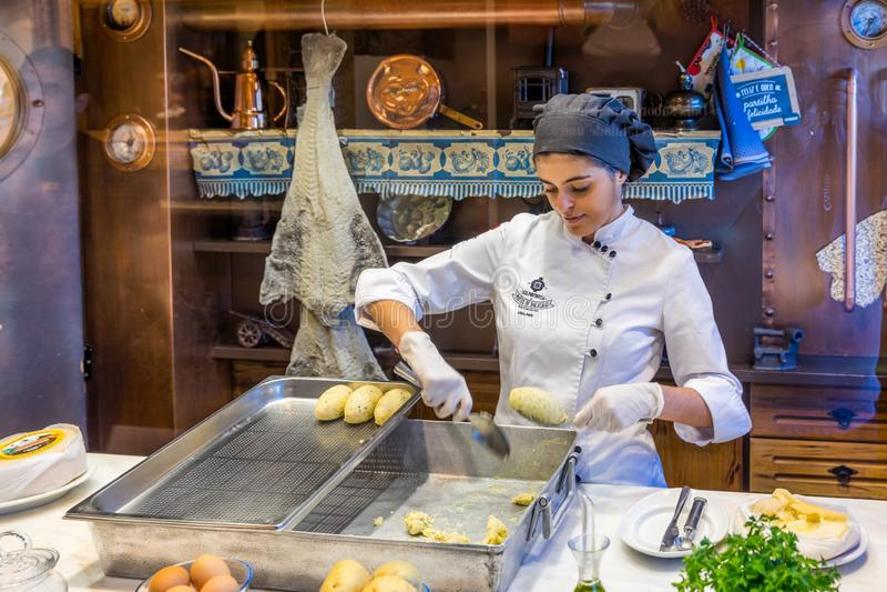 Porto Portugal - November 15, 2017: Den oidentifierade personalen förbereder codfishkakan i casaen Portuguesa gör Pastell de Baca royaltyfri bild