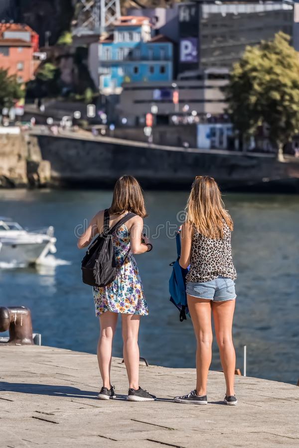 View of two young girls looking at the Douro river. Porto / Portugal - 10/02/2018 : View of two young girls looking at the Douro river royalty free stock photo