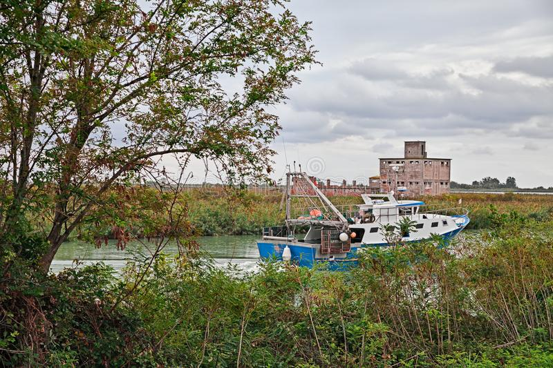 Porto Tolle, Veneto, Italy: view of the Po Delta Park with a fishing boat in the river stock photography