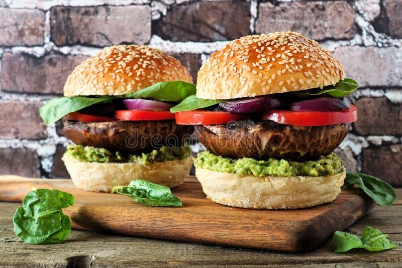 Portobello mushroom vegan burgers on a wood serving board against a dark brick background stock image