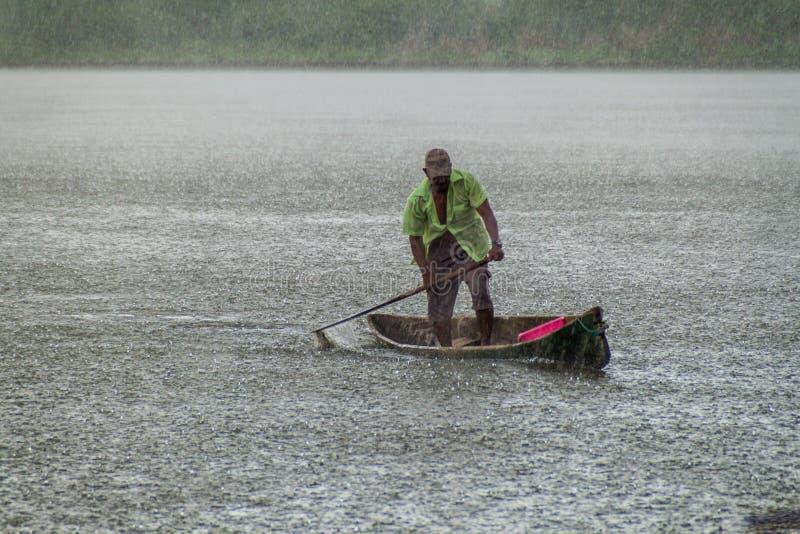 PORTOBELO, PANAMA - 28 MAI 2016 : Homme local dans son canoë pendant un rai lourd photo stock