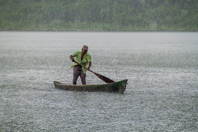 PORTOBELO, PANAMA - 28 MAI 2016 : Homme local dans son canoë pendant un rai lourd photo libre de droits