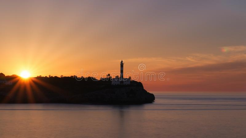 Portocolom-Leuchtturmsonnenaufgang, Schattenbild, schöner bunter Himmel, Sonnenstrahlen, ruhiger See, Mallorca, Spanien lizenzfreie stockfotografie