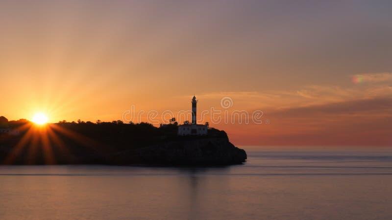 Portocolom lighthouse sunrise, silhouette, beautiful colourful sky, sun beams, calm sea, Mallorca, Spain royalty free stock photography