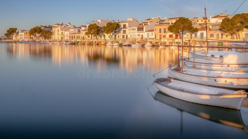 Portocolom radhus, hamn, port, guld- ljus, soluppgång, lugna blå medelhav, fiskebåtar, sandig strand, reflexion royaltyfri foto