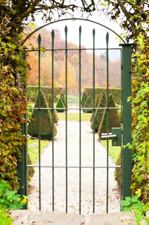 Portone antico del ferro con il giardino ornamentale di là fotografia stock