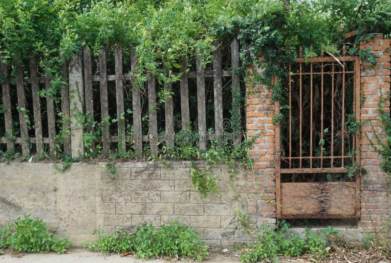 Portone arrugginito del ferro in un mattone antico e parete di pietra con la chiusura di legno immagine stock libera da diritti