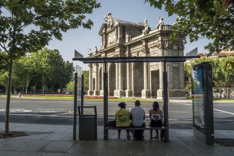 Portone di Alcala o Puerta de Alcala, tre viaggiatori che aspettano al fotografie stock libere da diritti