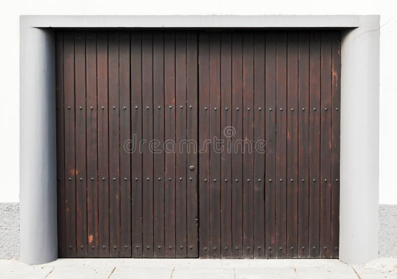 Portone di legno di Brown in muro di cemento bianco immagine stock libera da diritti