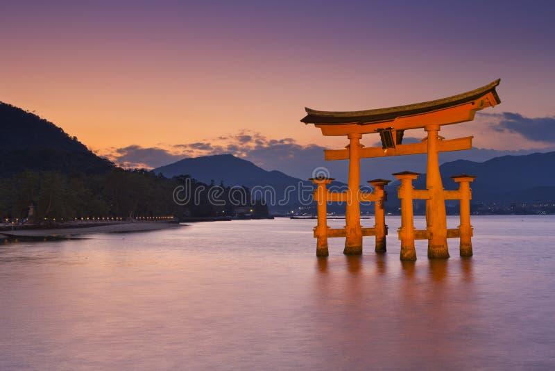 Portone di torii di Miyajima vicino ad Hiroshima, Giappone al tramonto fotografia stock libera da diritti