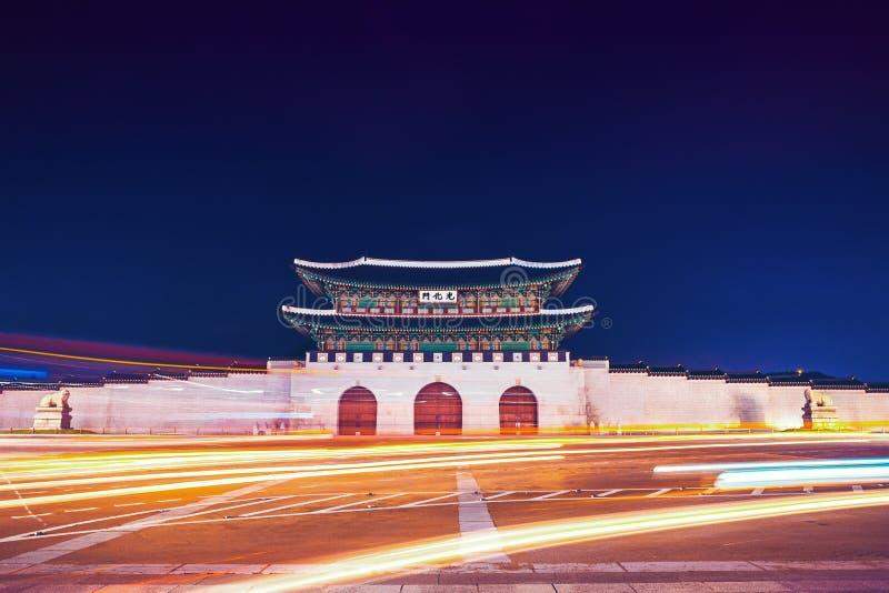 Portone famoso di Gwanghwamun del palazzo di Gyeongbokgung a Seoul, Corea del Sud con i fanali posteriori ed i fari delle automob fotografia stock