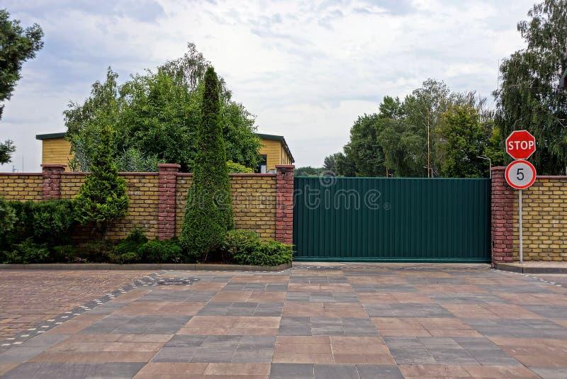 Portoni del ferro e segnali stradali verdi vicino ad un muro di mattoni con le piante ornamentali fotografie stock
