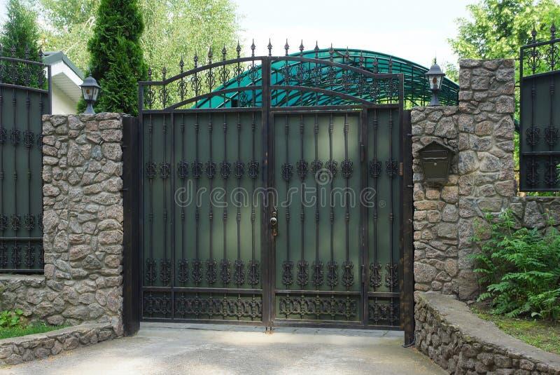Portoni grigi del metallo con il modello di cuoio nero e un recinto di pietra immagine stock libera da diritti