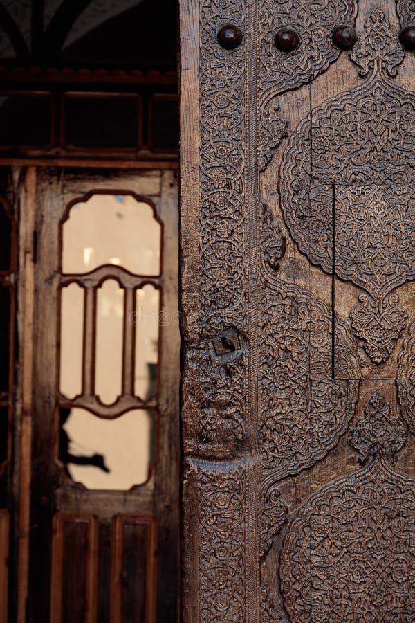 Portoni ornamentali di legno del madrasah del aminhon di Khiva Muhammad, fotografia stock libera da diritti