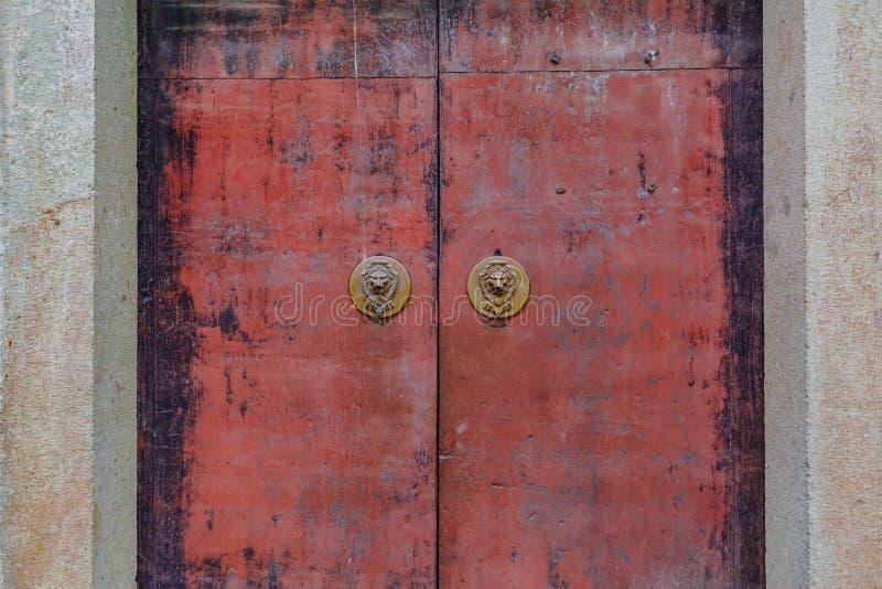 Portoni rossi strutturati del metallo con i battitori di porta capi del leone cinese immagine stock