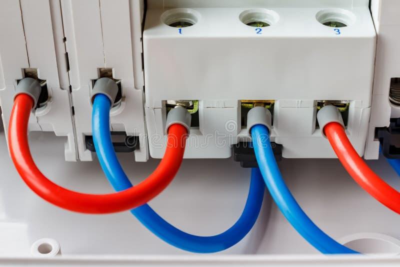 Portos dos interruptores automáticos instalados conectados pelo close up vermelho e azul dos fios foto de stock