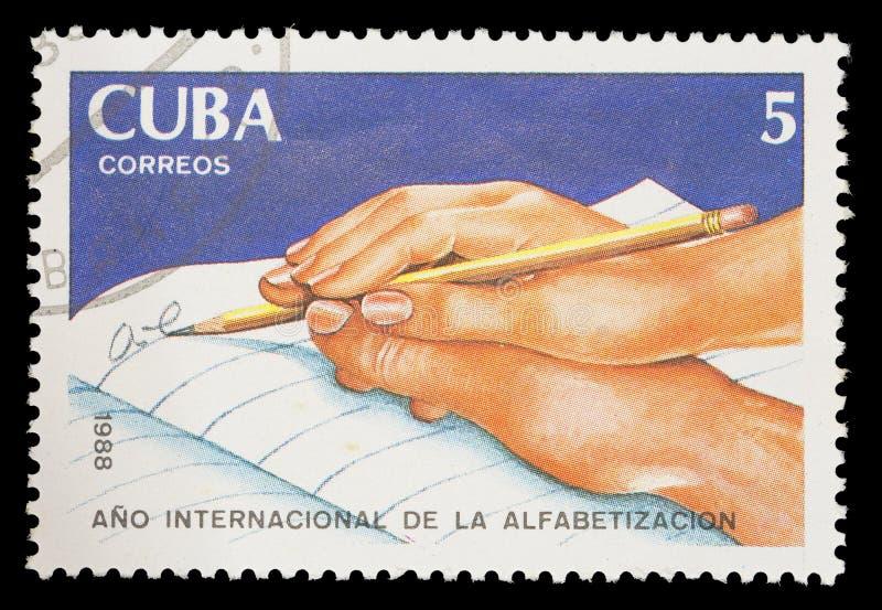 Portostämpeln som skrivs ut i Kuba, visar en handportion någon annars för att skriva, det internationella läs-och skrivkunnighetå arkivbilder