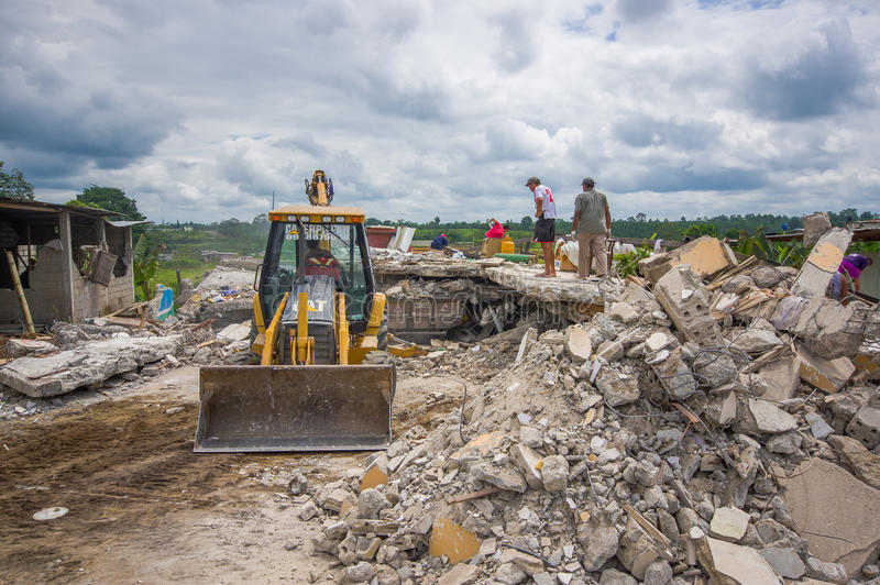 Portoviejo, Ecuador - April, 18, 2016: Rubble of a destroyed house after 7.8 earthquake, heavy machinery removes the stock photos