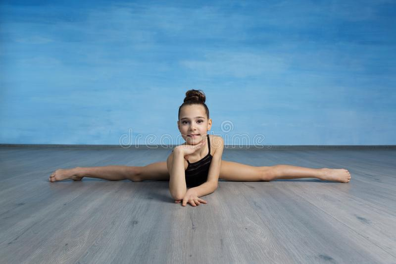 A portpait girl gymnast in a black gymnastic swimsuit is sitting on a cross splits stock photos