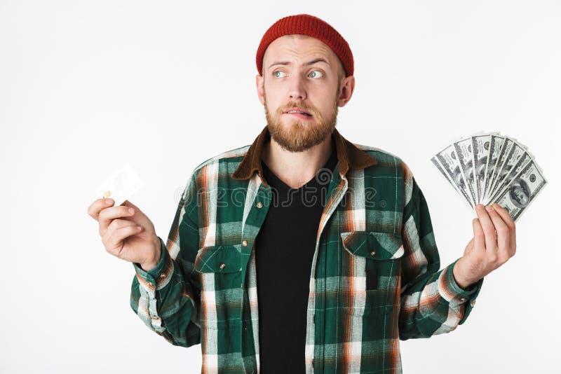 Porträt der attraktiven Mannholdingkreditkarte und Fan des Dollargeldes, bei der Stellung lokalisiert über weißem Hintergrund lizenzfreies stockfoto