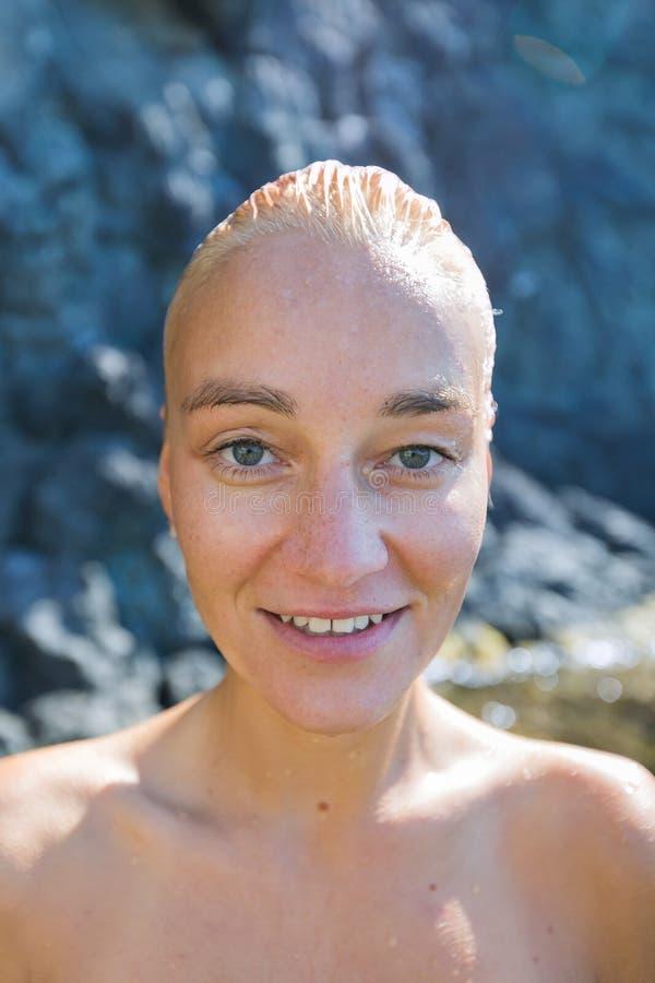 Porträt der attraktiven weiblichen Person mit dem nass slicked Haar und der bloßen Schultern gegen Küstenfelsen stockfotos