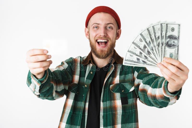 Porträt der begeisterten Mannholdingkreditkarte und Fan des Dollargeldes, bei der Stellung lokalisiert über weißem Hintergrund lizenzfreie stockfotos