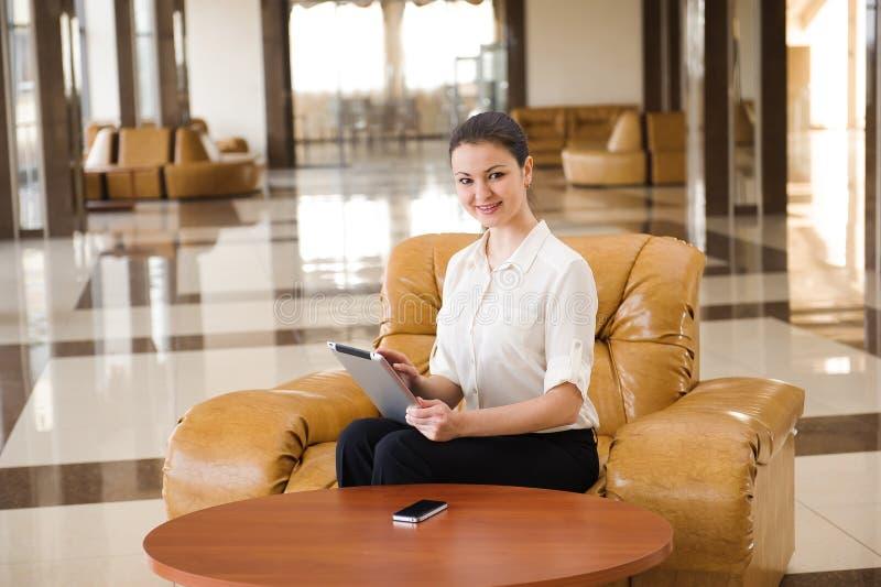 Porträt der beschäftigten Geschäftsfrau, die an ipad beim Sitzen am Sofa arbeitet stockfotografie