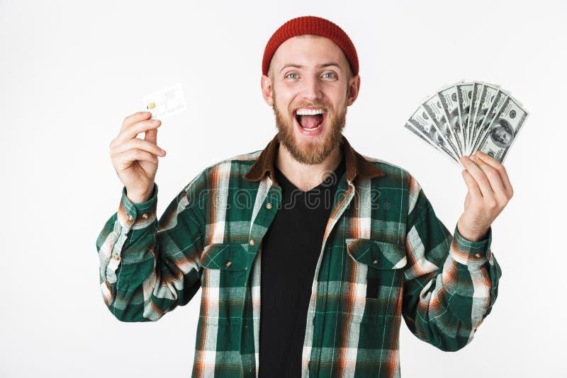 Porträt der erfolgreichen Mannholdingkreditkarte und Fan des Dollargeldes, bei der Stellung lokalisiert über weißem Hintergrund lizenzfreies stockbild