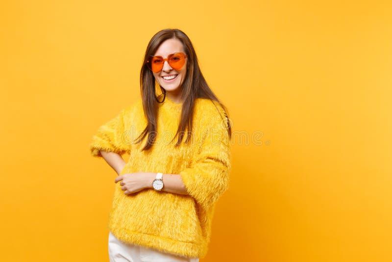 Porträt der glücklichen lächelnden jungen Frau in der Pelzstrickjacke, weiße Hosen, orange Brillenstellung des Herzens lokalisier lizenzfreie stockfotografie