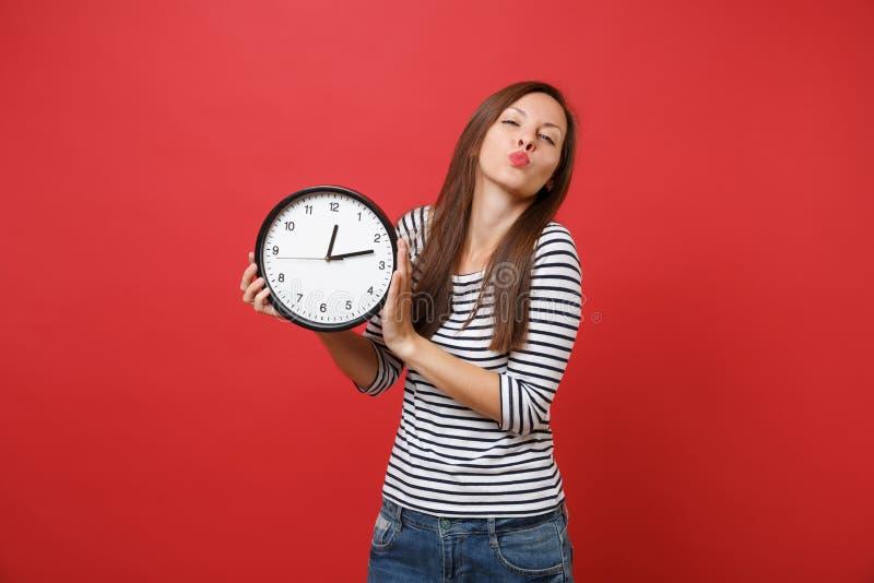Porträt der hübschen jungen Frau in der gestreiften Kleidung, die Küsse durchbrennt, senden den Luftkuß und halten runde Uhr loka stockbilder