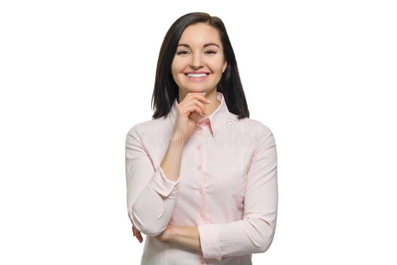 Porträt der jungen überzeugten lächelnden Frau herein mit den gefalteten Händen auf weißem lokalisiertem Hintergrund lizenzfreie stockbilder