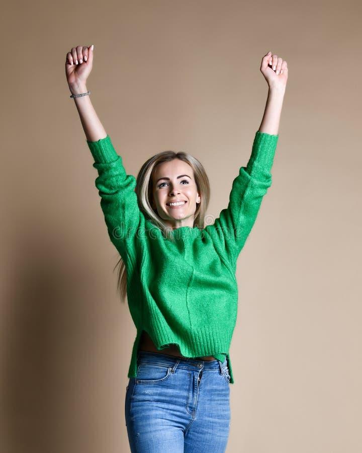 Porträt der jungen kaukasischen, süßen, erfolgreichen Frau, die Sieg mit den angehobenen Fäusten, lächelnd feiert stockbild