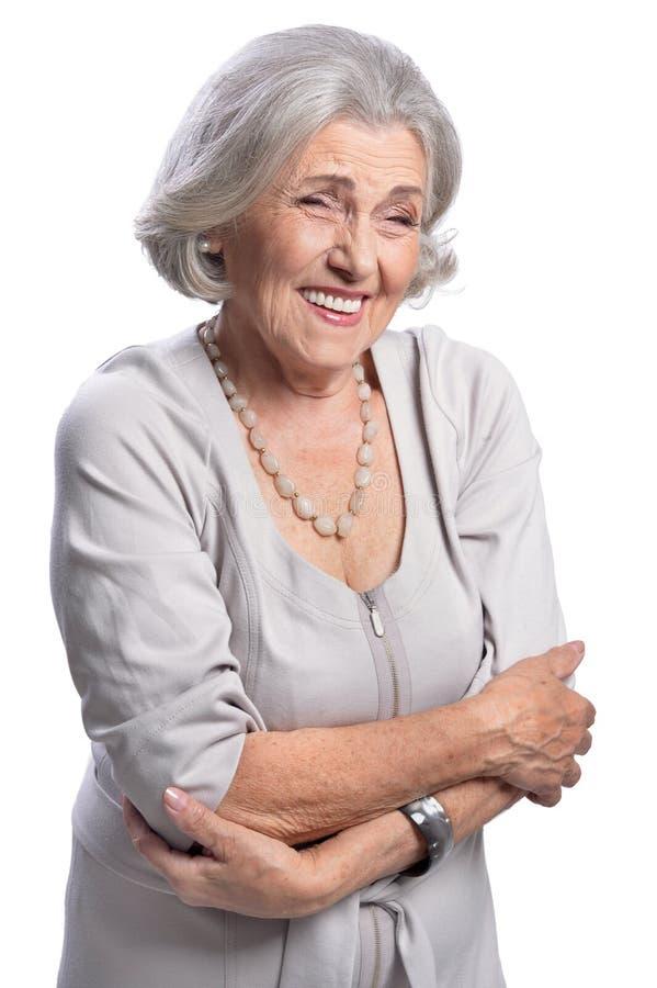 Porträt der schönen älteren Frau, die auf weißem Hintergrund lacht lizenzfreie stockbilder