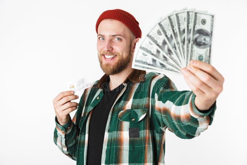 Porträt der unshaved Mannholdingkreditkarte und Fan des Dollargeldes, bei der Stellung lokalisiert über weißem Hintergrund stockfoto