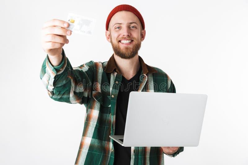 Porträt des Hippie-Mannes silbernen Laptop und Kreditkarte halten, bei der Stellung lokalisiert über weißem Hintergrund stockfotografie