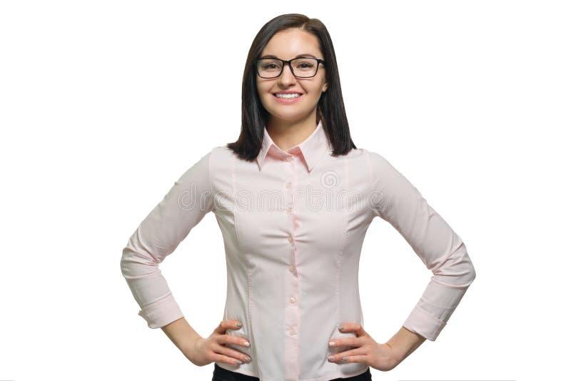 Porträt des jungen überzeugten lächelnden tragenden rosa Hemdes der Gläser der Frau auf weißem lokalisiertem Hintergrund stockbild