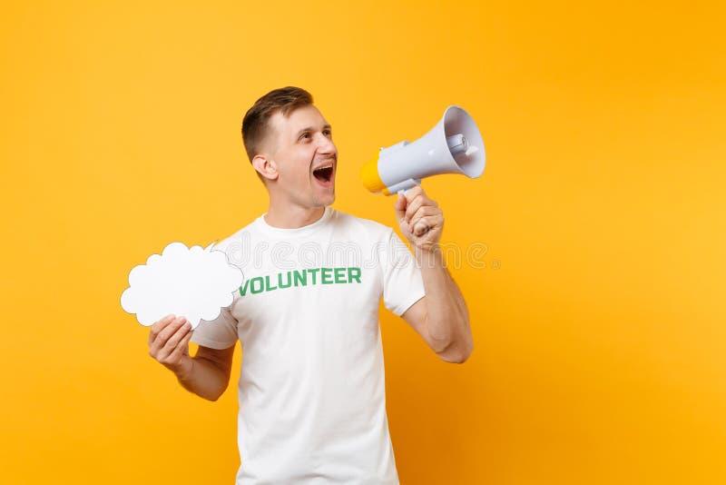 Porträt des jungen Mannes des Spaßes im weißen T-Shirt mit schriftlichem Aufschriftgrüntitel freiwilliger Schrei im Megaphon loka stockfoto
