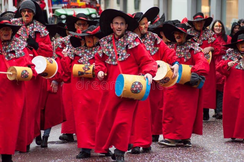 Porträt des lächelnden Musikers mit dem roten Kostüm, das Trommeln in der Straße spielt lizenzfreies stockfoto