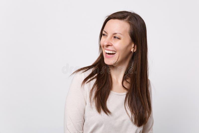 Porträt des Lachens der frohen attraktiven jungen Frau in der hellen Kleidung, die, beiseite schauend auf weißer Wand steht lizenzfreie stockfotos