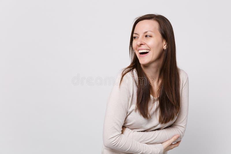 Porträt des Lachens der netten jungen Frau in der hellen Kleidung, die beiseite schaut, Händchenhalten faltete sich auf Weiß stockfotos