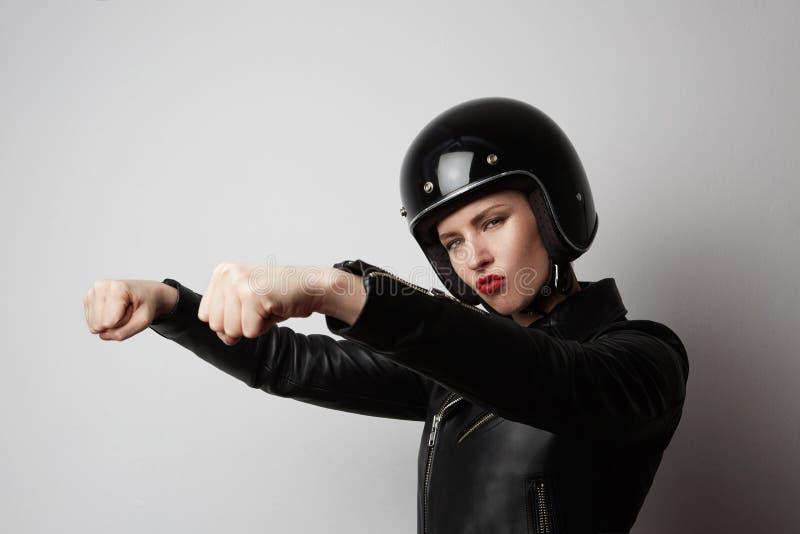 Porträt des schönen blonden Mädchens der Mode in der schwarzen Lederjacke vortäuschend, ein Motorrad auf Weiß vorbei zu reiten lizenzfreies stockbild