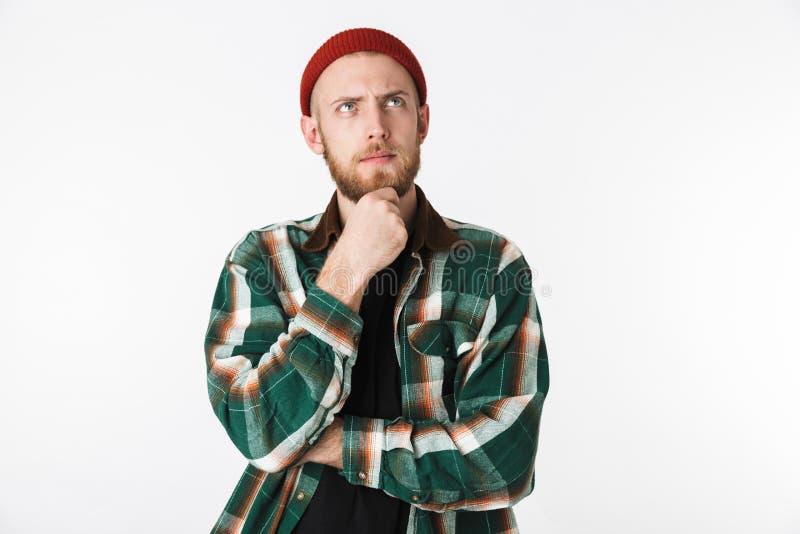 Porträt des tragenden Hutes und des karierten Hemds des kaukasischen Kerls, die oben, bei der Stellung lokalisiert über weißem Hi stockfoto