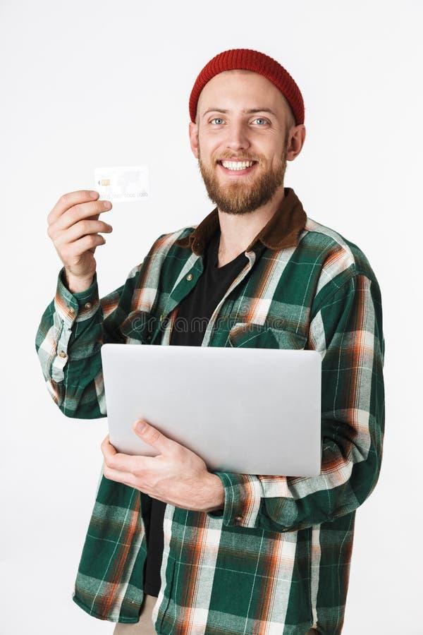 Porträt des unshaved Mannes silbernen Laptop und Kreditkarte halten, bei der Stellung lokalisiert über weißem Hintergrund lizenzfreies stockfoto