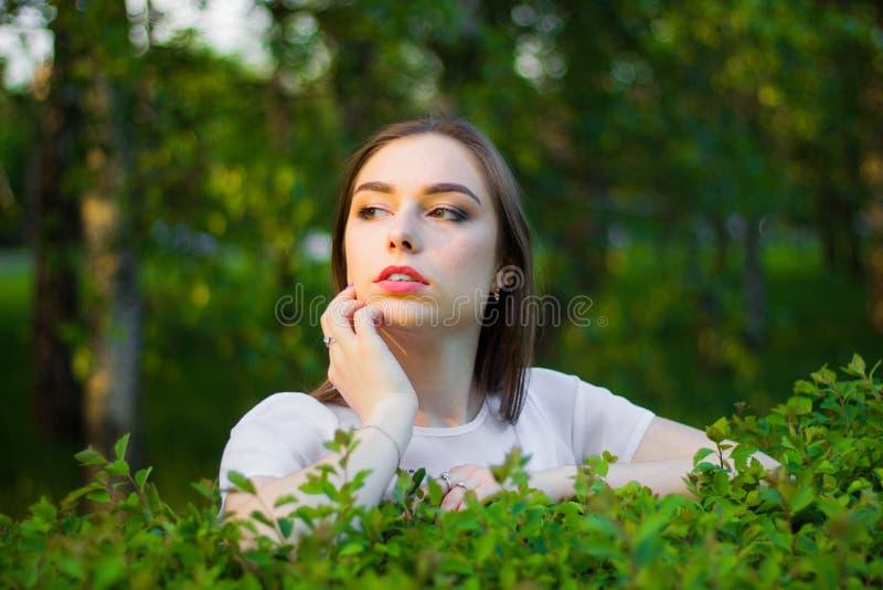 Porträt einer schönen jungen Frau auf einem Hintergrund von grünen Blättern, Sommer draußen Natürlich lächelnde Weile der Schönhe lizenzfreie stockfotos